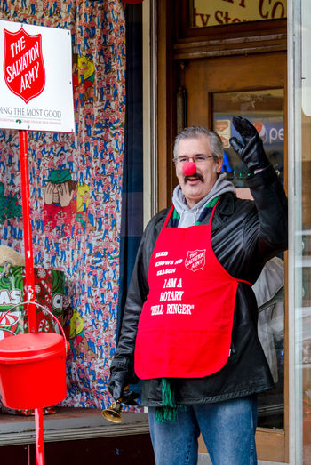 a salvation army bell ringer volunterrs his time to help people during the busy Christmas season Bell Ringer Christmas Donations  Holiday Man Salvation Army Volunteering Winter Adult Architecture Building Exterior Day Giving Back Hard Workers Helping People Holiday Spirit Job Male One Person Outdoors People Red Red Kettle Standing