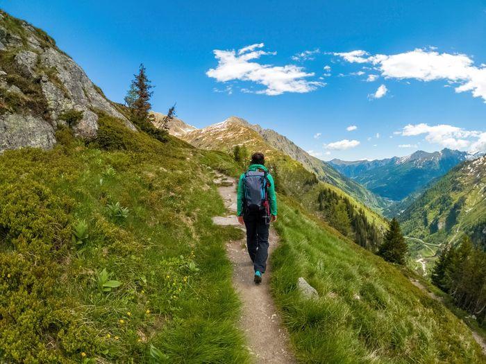 Woman hiking on footpath in the austrian alps near gastein, salzburg, austria