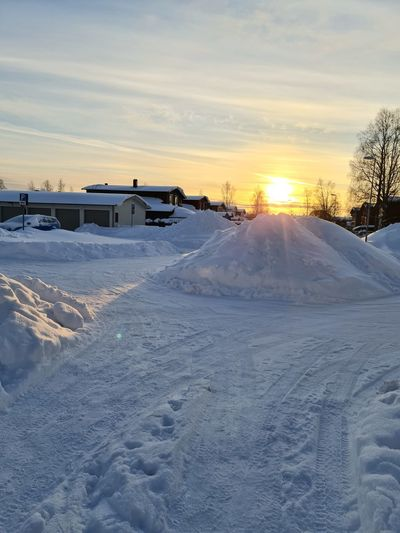 Snow covered land and houses against sky during sunset