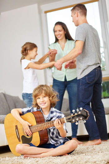 Portrait of smiling boy playing guitar while family playing in background at home
