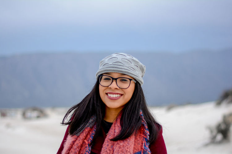 Portrait of smiling young woman standing on snow