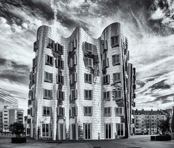 DUESSELDORF, GERMANY - JANUARY 20, 2017: One of the famous Ghery-Buildings in the New Media Harbor contrasts with the vivid sky in colour. B&w Dramatic Lighting Building Exterior Sky Architecture Cloud - Sky Built Structure City Building Nature Street No People Transportation Day Outdoors Low Angle View Mode Of Transportation Residential District Car Motor Vehicle Tree