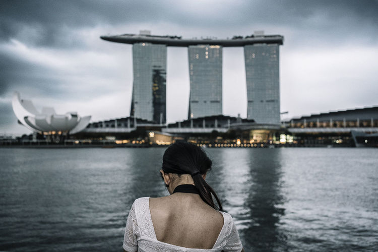 Rear View Of Woman By Marina Bay Sands Against Sky