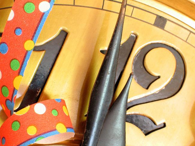 Uhr Zifferblatt mit Papierschlangen zum Jahreswechsel zeigt kurz vor Zwölf Close-up Indoors  Innen Innenaufnahme Jahreswechsel Kurz Vor Zwölf Luftschlangen Multi Colored No People No People, Party Party Time Prost Neujahr Silvester Silvesterparty Sylvesterparty Uhr Uhrzeiger Uhrzeit Zeiger Zifferblatt