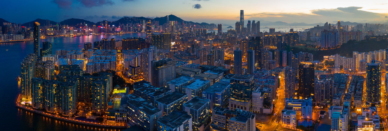 Panoramic view of illuminated buildings in city against sky at dusk