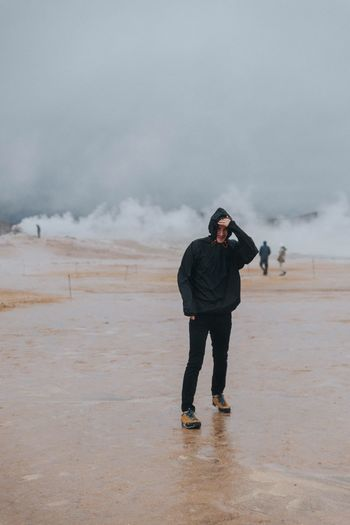 Full length of man standing at beach during stormy weather