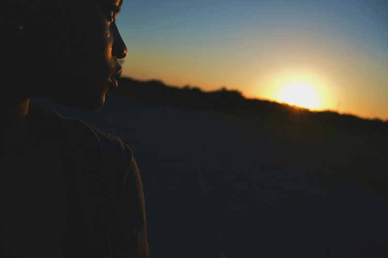 Cropped image of young woman against sky during sunset