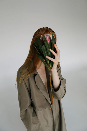 One Person Indoors  Studio Shot Young Adult Hairstyle Hair Lifestyles Front View Obscured Face White Background Wall - Building Feature Young Women Gray Background Waist Up Clothing Standing Casual Clothing Casual Fashion Fashion Model Fashion Photography Model Women Girls Flower Hand Holding Noface Hiding Redhead Gingerhair Girl Plant Flowering Plant Protea Springtime Decadence