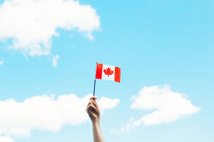 Human hand arm waving canadian flag against blue sky.  national canada day on 1st of july outdoor.