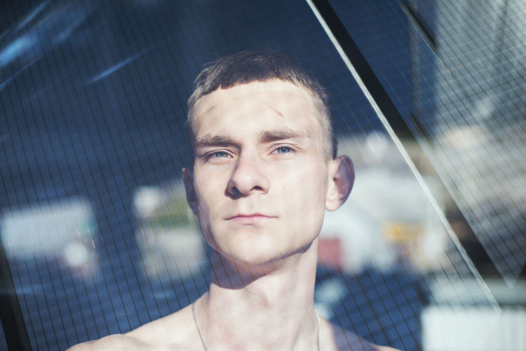 Portrait of handsome young man seen through window