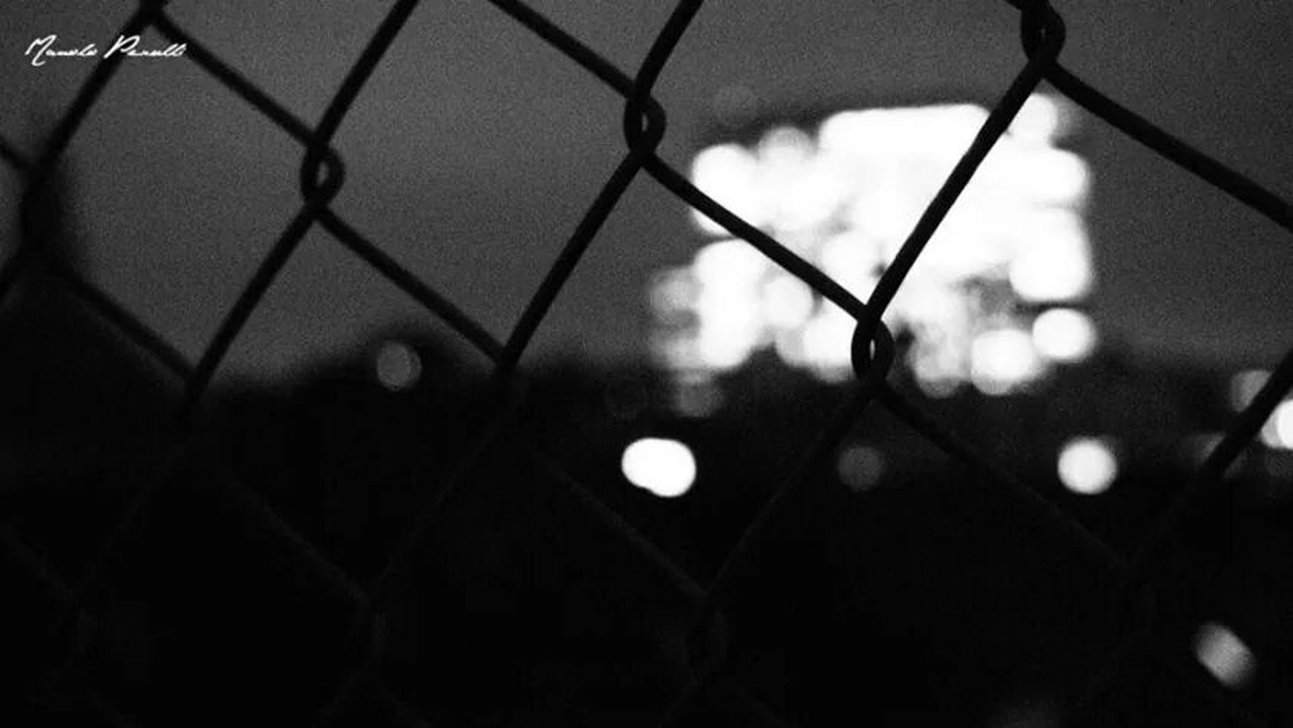 illuminated, chainlink fence, backgrounds, full frame, protection, safety, night, lighting equipment, fence, pattern, metal, low angle view, security, built structure, no people, focus on foreground, architecture, indoors, close-up, building exterior