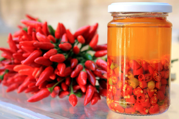 Bunch Of Chili Peppers And Pickle Bottle On Table