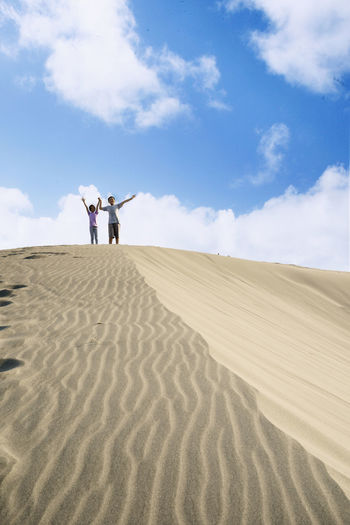 Adult Arid Climate Beauty In Nature Climate Cloud - Sky Couple - Relationship Day Desert Land Landscape Leisure Activity Men Nature Outdoors Real People Sand Sand Dune Scenics - Nature Sky Togetherness Two People Women