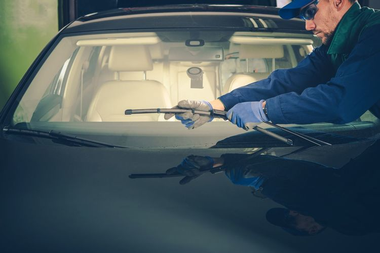 Mechanic cleaning car in workshop