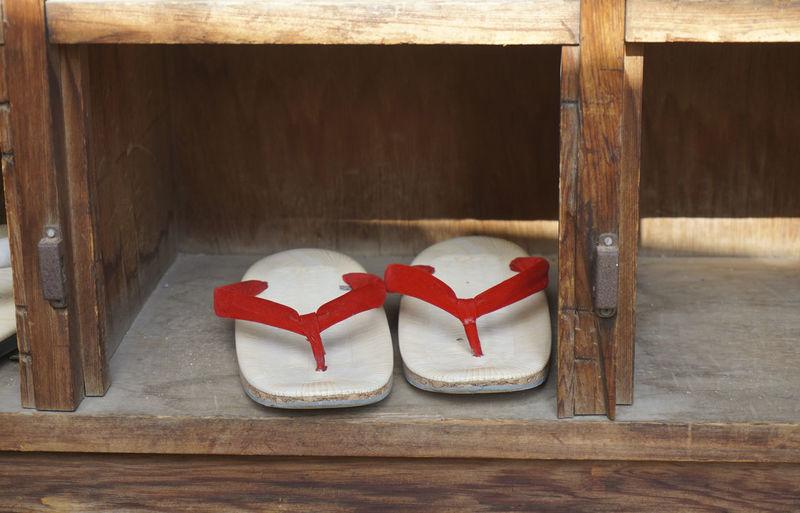 Close-up of flip-flops below wooden seat