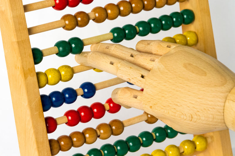 Close-up of wooden hand on abacus against white background