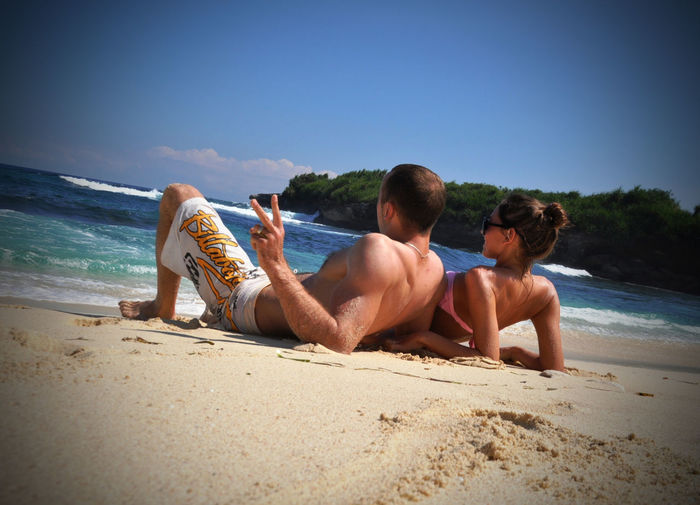 Tilt image of couple resting on beach against blue sky during sunny day