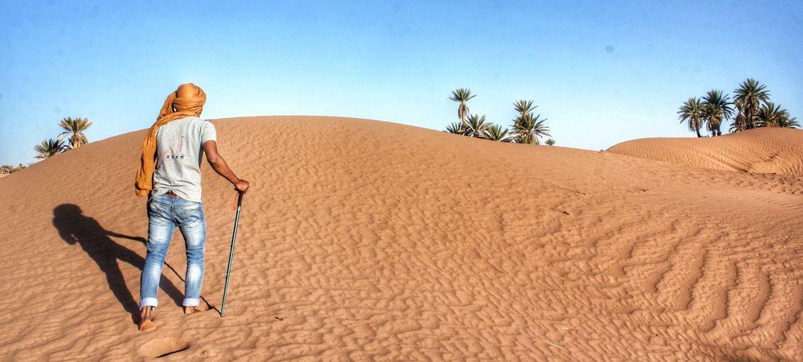 Rear view of man walking on sand dune at desert
