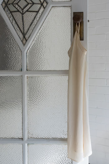 Close-up of white clothes hanging on wall