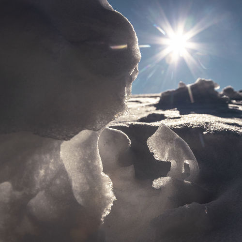 Close-up of snow on sunny day against sky