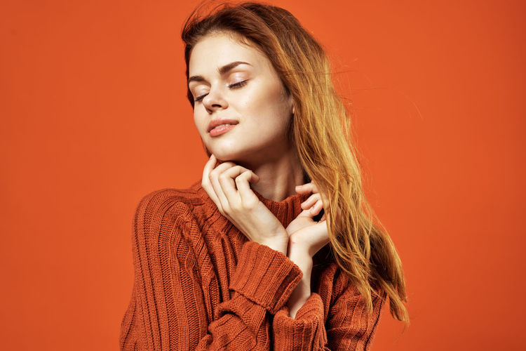 Portrait of beautiful young woman against orange background