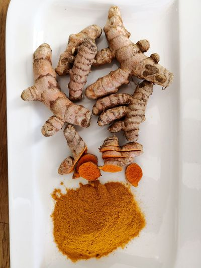 Turmeric powder and curcuma roots on white plate background Seasoning Curry Powder Curcuma Curcuma Longa Curcuma Root Curcumin Curcumin Root Curcuma Powder Superfood Health Benefits Health Benefits Anise Stack Variation Close-up Food And Drink Dried Food Turmeric  Ground - Culinary Spice Ginger Dried Fruit Legume Family