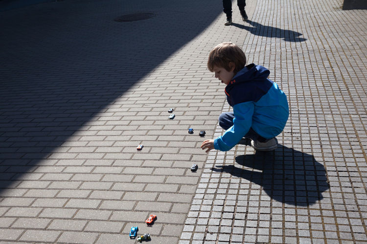 High angle view of boy playing with toy cars on footpath