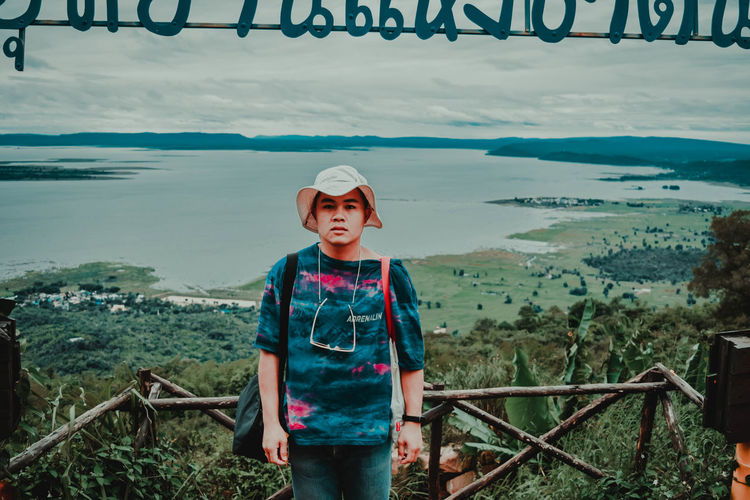 Portrait of boy standing on railing against sea