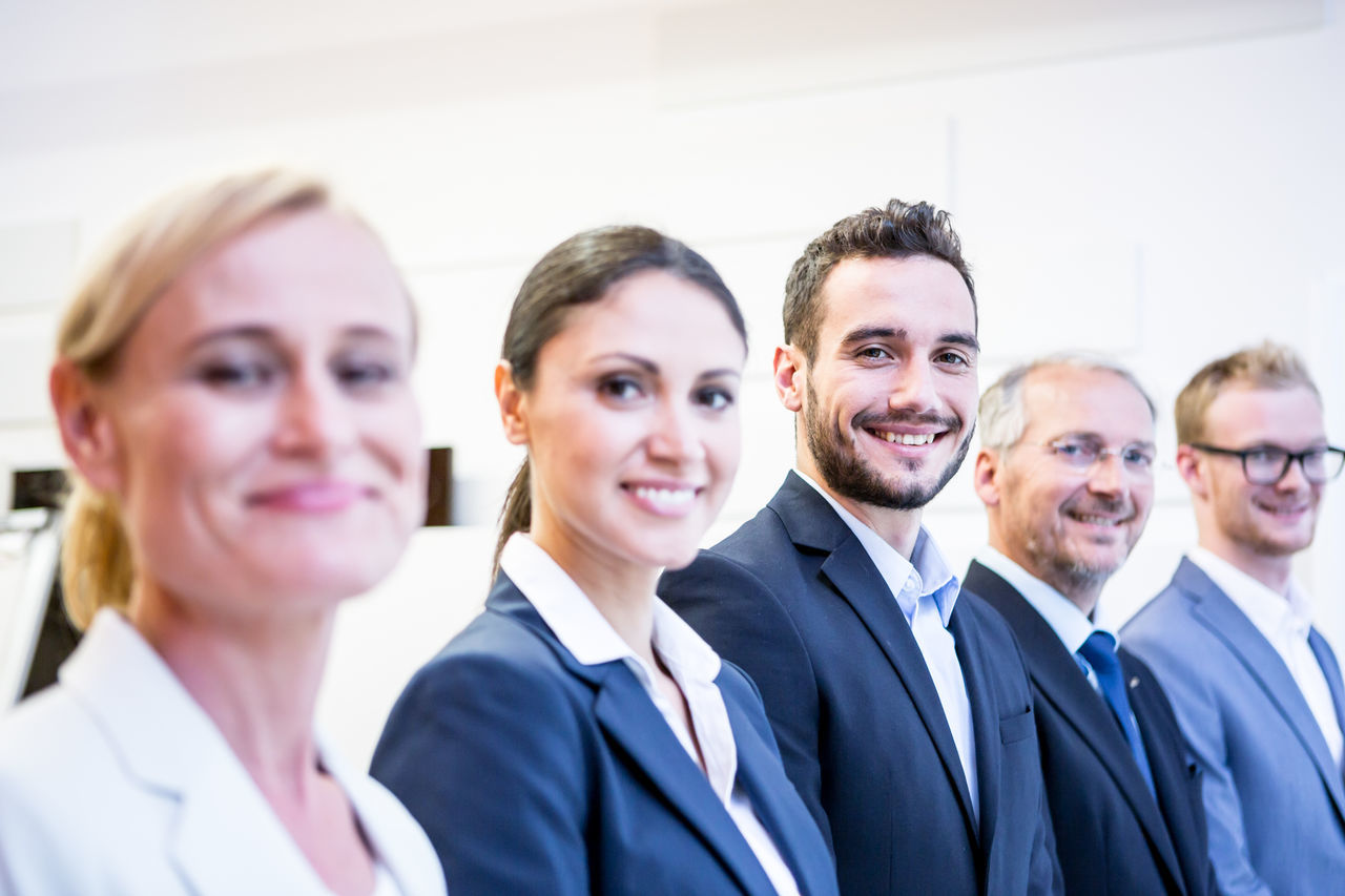 Portrait Of Smiling Business People Standing Side By Side In Office