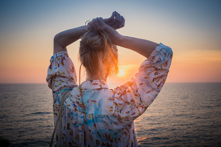 Rear View Of Woman With Hands Over Head By Sea During Sunset