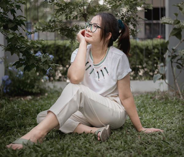 Thoughtful woman sitting on grass outdoors