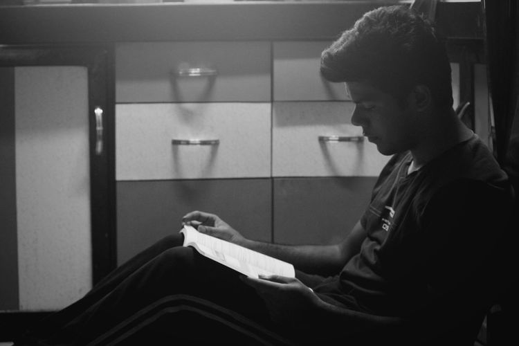 Side View Of Young Man Reading Book