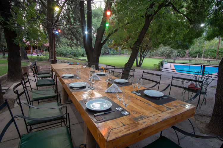 High angle view of empty chairs and table against trees