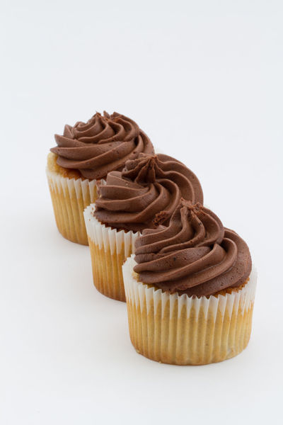 Three chocolate cupcakes in a row with chocolate frosting or icing on an isolated white background. Portrait orientation. Bake Bakery Baking Bun Buns Cakes Chocolate Chocolate♡ Cupcake Cupcakes Diet Frosting Iced Icing Indulgence Overindulgence Sugar Sugary Sweet Sweet Food Swirl Treat Unhealthy Eating Unhealthyfood White Background