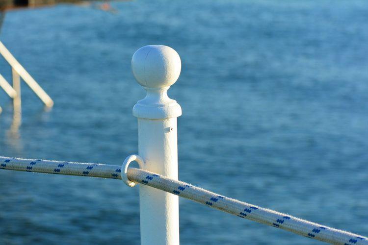 Close-up of metal railing against sea