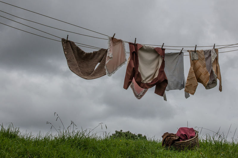 Low angle view of clothesline against cloudy sky