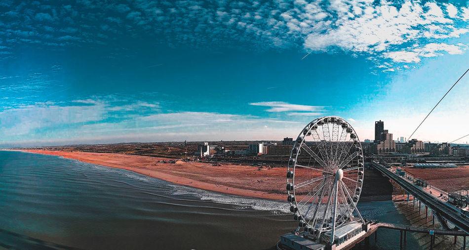 Amusement park by sea against blue sky