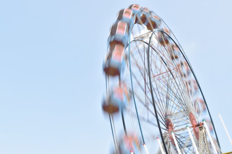 Low angle view of moving ferris wheel against clear sky