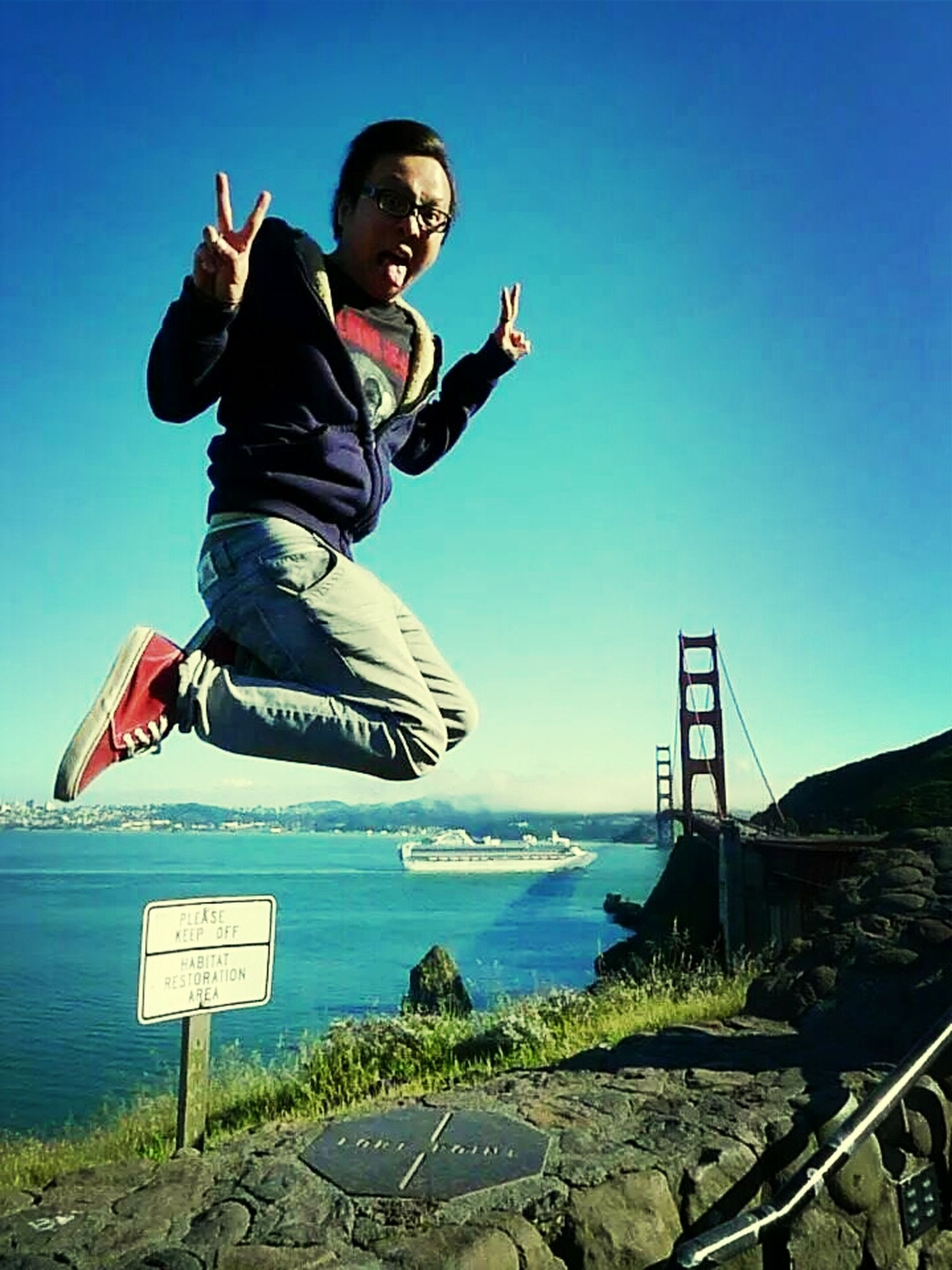 lifestyles, leisure activity, full length, young men, casual clothing, person, young adult, clear sky, blue, fun, enjoyment, copy space, mid adult men, jumping, smiling, vacations, low angle view, happiness