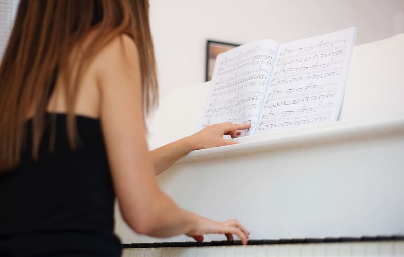 Rear view of young woman playing piano