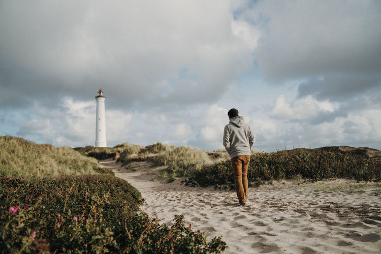 Man walking in front of lighthouse in Denmark Sky Cloud - Sky Rear View One Person Nature Standing Land Full Length Tower Men Lighthouse Beauty In Nature Real People Leisure Activity Day Scenics - Nature Plant Lifestyles Outdoors Denmark North Sea Dunes Hiking Holiday Moments The Week On EyeEm Editor's Picks