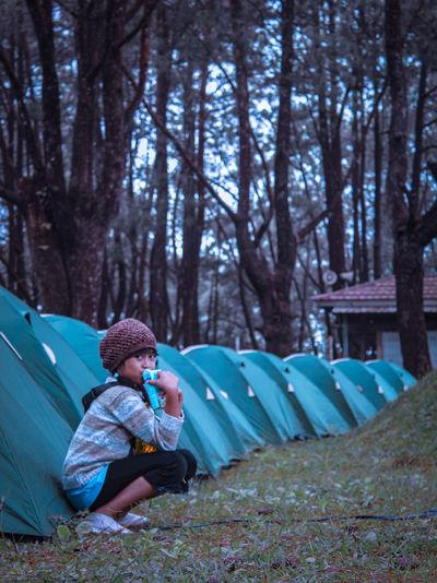 Woman sitting in tent on field
