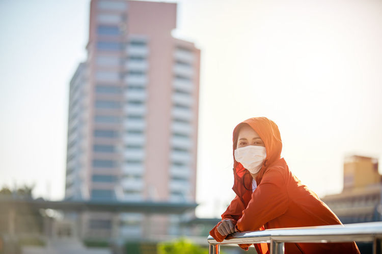 Portrait of young woman in front of office building
