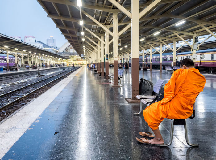 A buddhist monk wait train in platform at Bangkok station. Man backside who sit on chair, can not identify whom is he. Perspective image of railway at station. Travel by train in Thailand. Backside Architecture Casual Clothing Clothing Contemplation Full Length Illuminated Men Mode Of Transportation Mountain One Person Orange Color Public Transportation Rail Transportation Railroad Station Railroad Station Platform Railroad Track Rear View Sitting Track Train Transportation Travel Uniform Waiting
