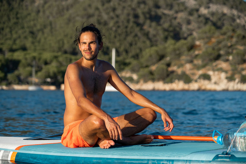 Portrait of young man sitting in sea