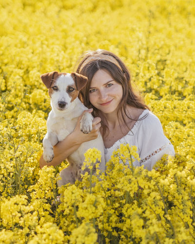Beautiful woman with dog amidst yellow flowers on field