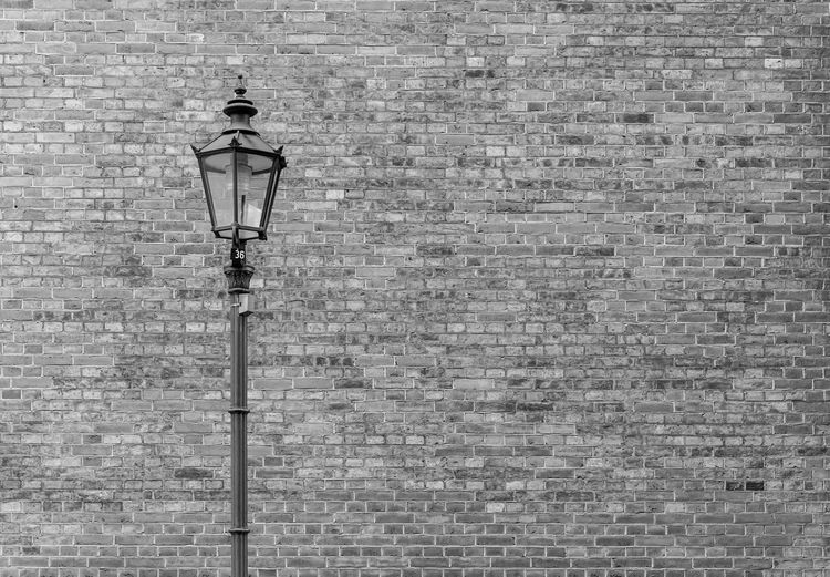 Low angle view of street light against brick wall