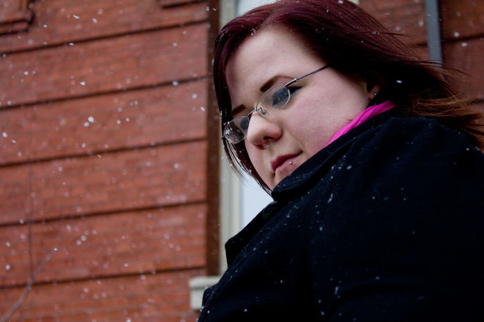 Beautiful Woman Outdoors Brick Wall Real People Portrait Pierced Snowfalling Light Snow Fall Thoughtful Introverted Ontario, Canada KitchenerOntario Red Hair Black Coat Black Jacket Scarf Contrast Cold Outside Rosy Cheeks Building Exterior Urban Photography Low Angle Shot Winter In The City City Life Walking Around The City