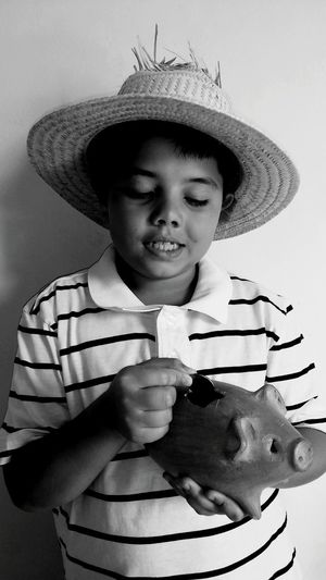 Boy With Hat Putting Coin In Piggy Bank