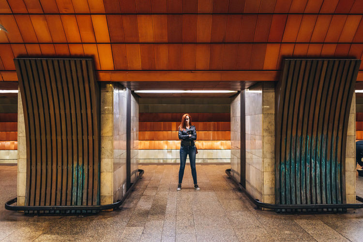 Full length portrait of woman standing in metro